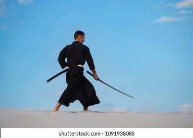 Focused man, in traditional Japanese clothes, with sword, katana, is training martial arts in desert during sunset - samurai on the blue cloudy sky background. Side view.