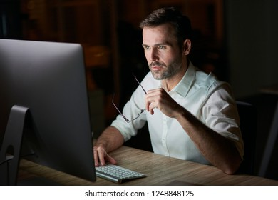 Focused man using computer at night