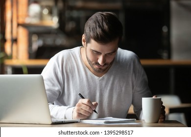 Focused man using laptop and writing notes, studying or working in cafe, student preparing for test or exam in cafe, writing research work, information in notebook, holding cup of coffee