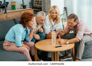 focused mature friends playing with wooden blocks at home