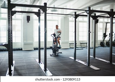 Focused mature man in sportswear riding a stationary bike while working out alone in a gym