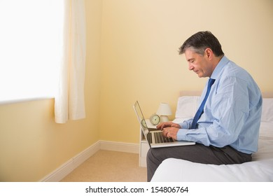 Focused mature man using a laptop sitting on a bed in a bedroom