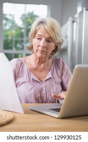Focused mature woman using her laptop and reading a file