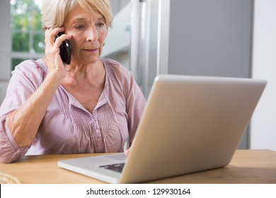 Focused mature woman using her laptop and calling