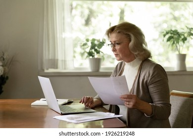 Focused middle aged woman holding document and using laptop at home. Female adult pensioner checking life insurance or savings financial account, paying bill on bank online app, planning budget