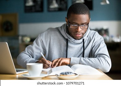 Focused millennial african american student in glasses making notes writing down information from book in cafe preparing for test or exam, young serious black man studying or working in coffee house