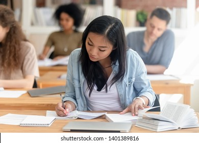 Focused millennial Asian female student sit in shared coworking space studying with handbook writing do homework, concentrated teen girl make notes in workbook prepare for test or exam in library