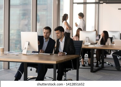 Focused millennial men sit at pc working together discussing project in shared workspace, diverse businesspeople busy using computers, preparing reports in coworking office. Cooperation concept