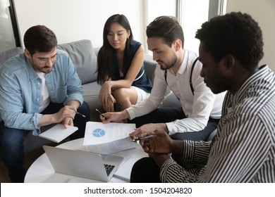 Focused millennial multiracial employees brainstorm at office meeting consider business plan company paperwork, diverse young businesspeople talk share ideas discuss report at briefing together