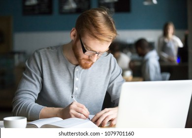 Focused millennial redhead student writing down summary studying in cafe with laptop and book preparing for test exam, serious businessman or writer making notes about new idea working in coffee shop