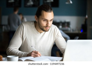 Focused millennial student study with laptop and books sitting out in café, serious male writing in notebook working at computer in coffeeshop, concentrated young man prepare homework in coffeehouse