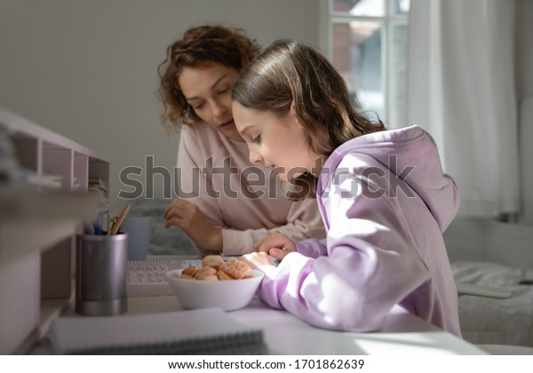 Focused mom helping teenage daughter doing homework studying from home. Young adult parent mum or tutor, coach teaching school child, explaining distance learning education reading book together.
