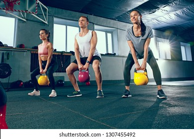 The focused and motivated strong young fitness men and women in sportswear doing exercises crouching with the kettlebells at the gym. Healthy lifestyle concept