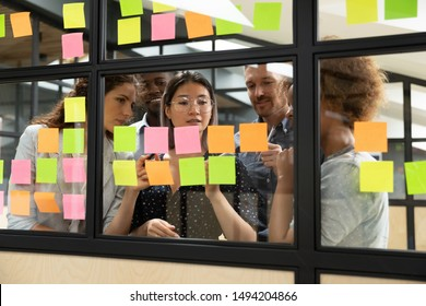 Focused multiethnic business team people brainstorm on corporate project together write strategy tasks on post in sticky notes stand behind glass wall, diverse staff group planning management concept