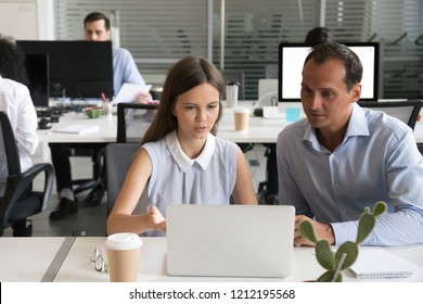Focused office colleagues discussing online project looking at laptop screen, female employee explaining computer task to male coworker talking working together, help and mentoring teamwork concept