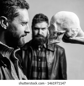 Focused on breaking fear. Psychology concept. Human fears and courage. Looking deep into eyes of your fear. Man brutal bearded hipster looking at skull symbol of death. Overcome your fears. Be brave.