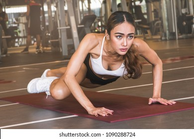 Focused on core body workout. Women exercising in gym on the yoga mat doing plank and moving leg to the side.