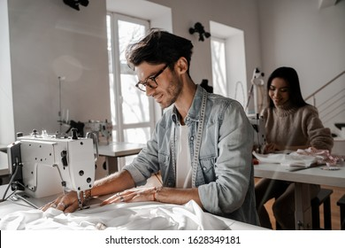 Focused on the sewing process tailors sit sewing at their sewing machines. Sewing, design work, tailoring studio, tailor, designer clothes, manufactory, in the process of creative development