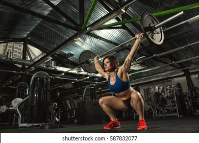 Focused on success. Low angle shot of an attractive strong muscular female bodybuilder doing heavy duty squats lifting barbell at the gym copyspace motivation crossfit fitness sport activity training