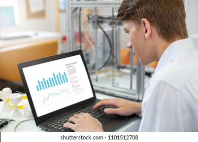 Focused on work. Pleasant young man sitting at the table in the office and working on the laptop, creating a presentation