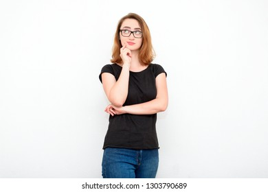 Focused pensive red-haired woman on a light background in casual clothes makes the decision and thinks.