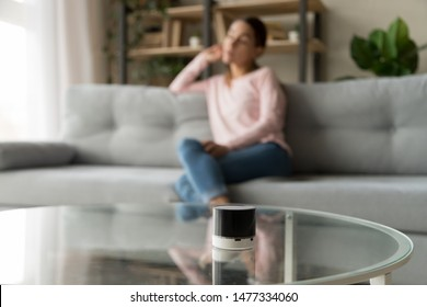 Focused picture of new modern stylish compact voice assistant speaker or portable wireless speaker on table with unfocused blurred young woman relaxing on couch in living room at home on background.