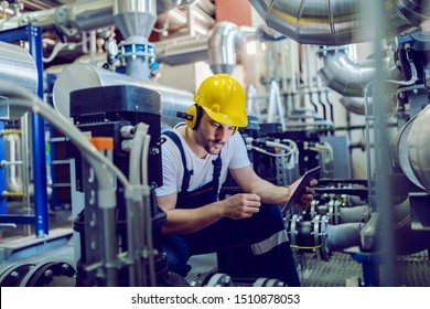 Focused plant worker in overalls, with protective helmet on head and antiphons on ears using tablet for checking machine while crouching.