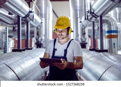 Focused plant worker in overalls, with protective helmet on head and antiphons on ears using tablet for checking machine.