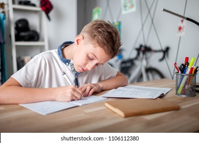 Focused preteen boy doing homework on desk in his room