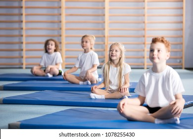 Focused pupils sitting cross-legged on blue mats during gymnastics class
