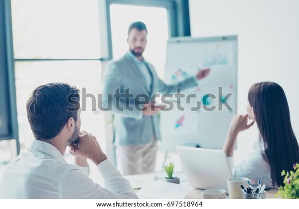 Fokussierte Hinteransicht von drei Kollegen, auf Daten im Flipchart konzentriert, Lösungen für die Probleme ihres Unternehmens diskutiert und Meinungen und Ideen austauschen