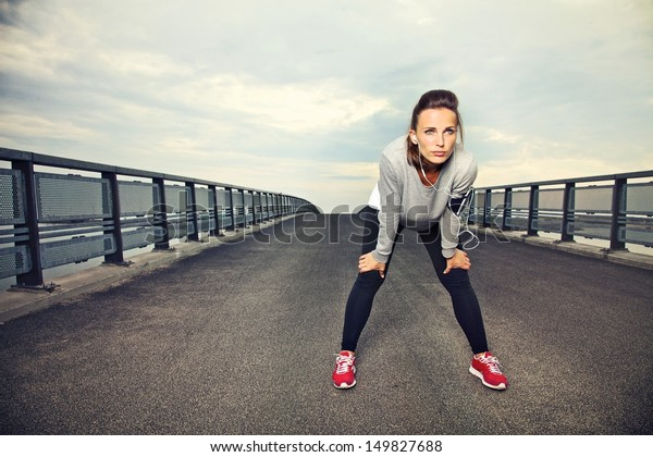 Focused runner outdoors resting on the bridge