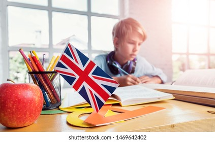 Focused schoolboy studying english reading textbook in classroom