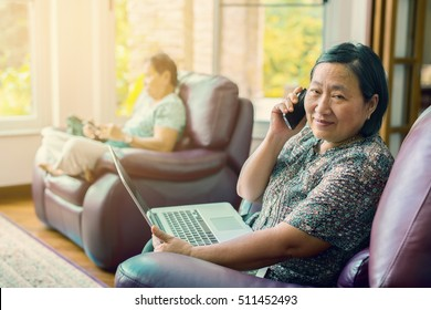 Focused senior asian woman talking on the mobile phone and  using laptop in living room at home. (lens blur effect and vintage color toned image)