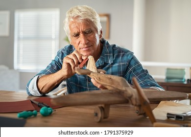 Focused senior man using sandpaper to polish wooden airplane sculpture. Mature carpenter working on making wooden flight at home. Happy old grandfather at home busy making handmade sculpture.
