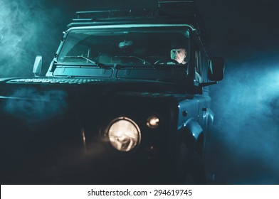 Focused Senior Middle Aged Guy Driving his Vintage 4x4 Vehicle Alone on a Fuzzy Dark Night.