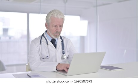 Focused Senior Old Doctor Working on Laptop