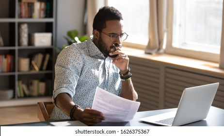 Focused serious african american businessman accountant analyst holding documents looking at laptop computer screen doing online trade market tech research thinking working sit at home office desk