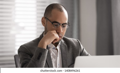 Focused serious african businessman in suit thinking solving business work problem looking at laptop screen, thoughtful puzzled male professional executive concentrating managing risks using computer