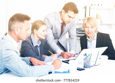 Focused serious business team working with computer in modern office
