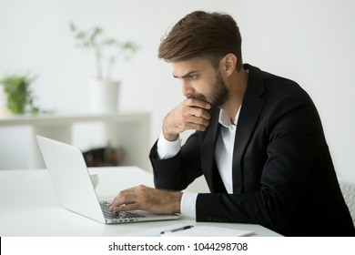 Focused serious businessman in suit thinking reading online news or solving business problem working on laptop looking at screen, worried puzzled executive managing stock market risks using computer
