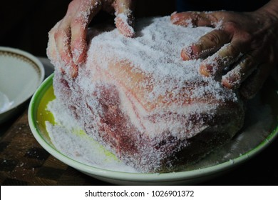A focused shot of hands covered in salt rub spreading the salt rub on a pork butt sitting in a green and yellow bowl.