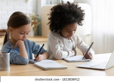 Focused small diverse sisters sitting at table, doing tasks in notebooks together at home. Busy little mixed race kids girls involved in preparing school homework or enjoying online educational class.
