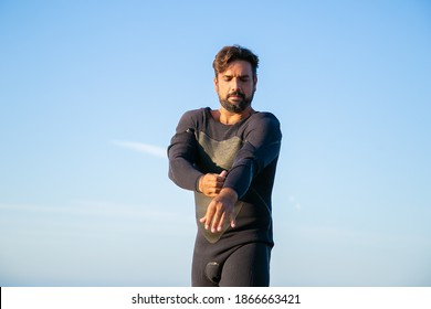 Focused sportsman putting on wetsuit for surfing on ocean beach. Low angle, blue sky background. Active lifestyle concept