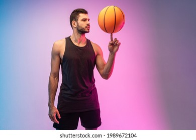 Focused sportsman spinning basketball ball on finger. Young bearded european basketball player. Isolated on blue and pink background. Studio shoot. Copy space