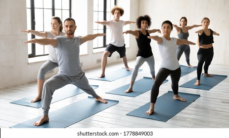 Focused sporty handsome young male trainer leading yoga class for concentrated multiracial students, practicing virabhadrasana second warrior II position together at yoga training in modern studio.