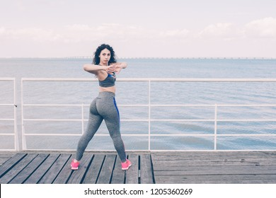 Focused sporty young Latin woman exercising on bridge with bay or river in background. Sexy fit girl enjoying street workout. Fitness and healthy lifestyle concept