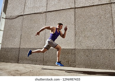 Focused Strong Sporty Man Running Fast on Road.