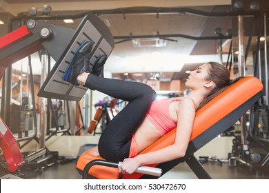 Focused strong young sportswoman doing fitness exercises for legs muscles in gym
