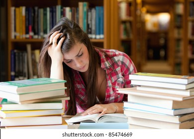 Focused student surrounded by books in a library